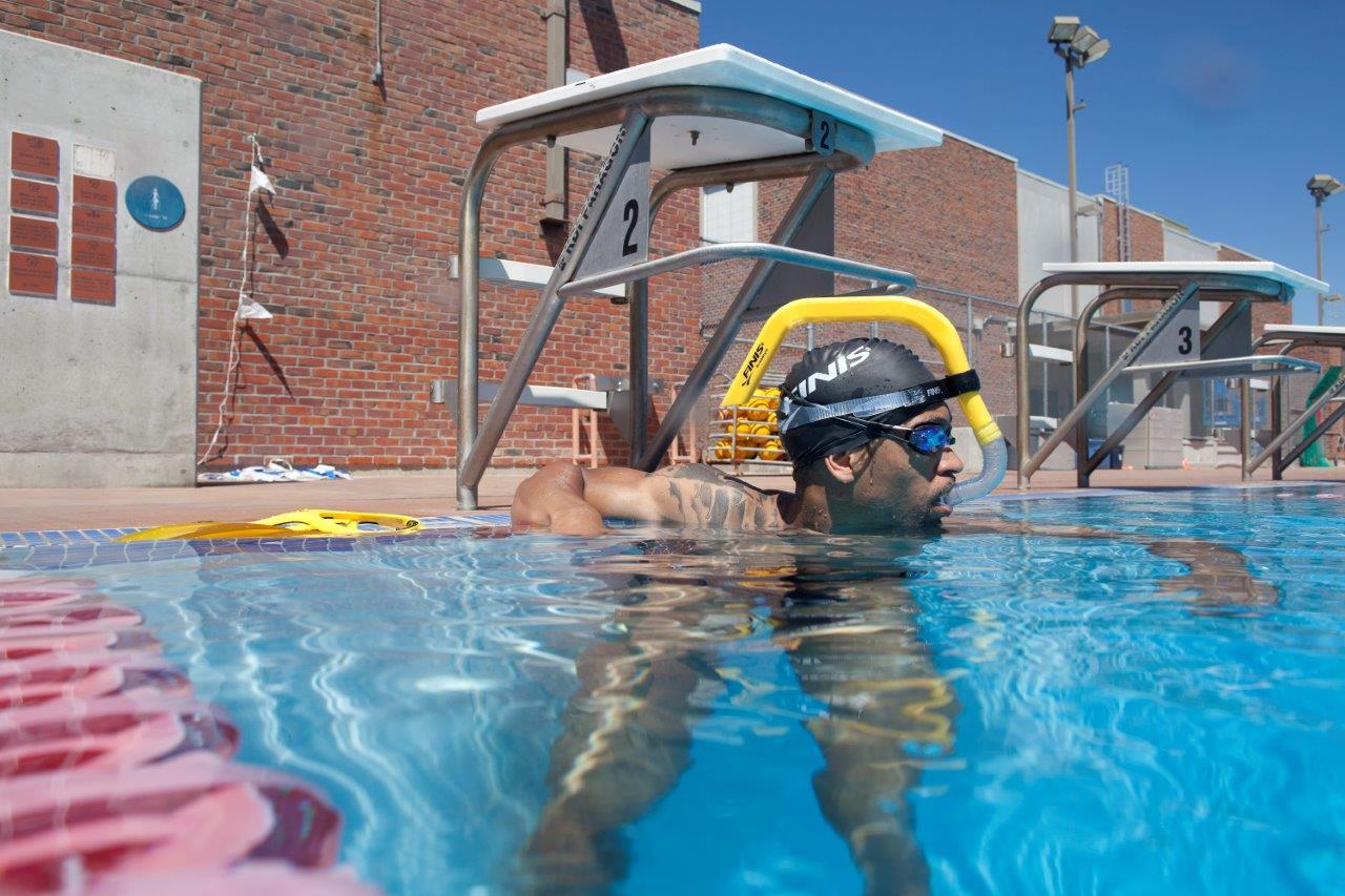 Centrální šnorchl Finis, který je zahnutý kolem hlavy plavce.